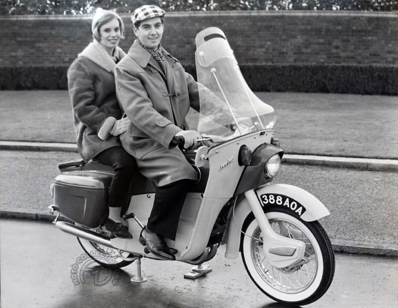L'ingénieur Bob Trigg passé de la planche à dessin au parking de l'usine pour les photos publicitaires avec mannequin et moto est sur cales !