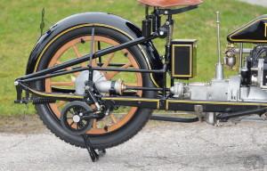 Une commande complexe par pédale permet d'abaisser les roulettes stabilisatrices. Il n'y a qu'un frein arrière à bande et la transmission s'effectue par arbre et couple conique. Notez aussi la suspension de la selle sur tube télescopique.
