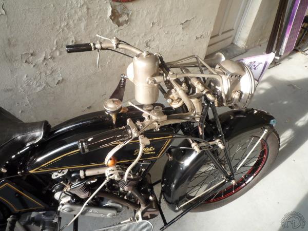 Un renvoi sur la colonne de direction est relié à un frein sur le tube supérieur du cadre et la poignée de gaz tournante présente sur les premiers modèles de salon a laissé place à de classiques manettes.