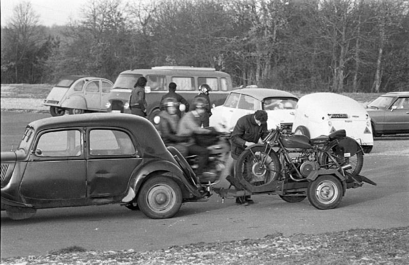Une rare rencontre se prépare lors d'une rencontre du club du Motocyclettiste sur le circuit de Dijon Prenois en 1976 entre Marc Defour penché sur sa Guzzi quatre soupapes qu'il va descendre de sa remorque et Jean Nougier qui vient d'arriver derrière avec sa DS attelée de sa remorque 3 moto du même métal (c.a.d. enentièrement faite avec des capots de DS en aluminium !).