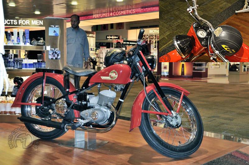 Même petite, l'Harley garde son prestige et cette Hummer 165 cm3 de 1953 reconnaissable à son carbu sous carter était exposée dans une pharmacie de l'aéroport de Singapour. Sous le couvre-chef  de l'heureux pharmacien se cachent deux bouchons, pour l'essence et pour le réservoir d'huile intégré.