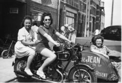 Deux Jeunes filles prennent la pose sur une Souplex sur la côte belge et la maman, derrière, les surveille  encastrée dans le triporteur du garage.